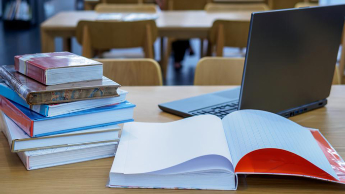 Stack of books on table top in the library / Education & Back to school concept